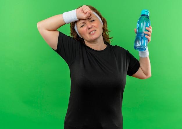 Donna sportiva di mezza età in maglietta nera con fascia tenendo una bottiglia di acqua che sembra stanca con l'espressione infastidita che tocca la sua testa in piedi sopra il muro verde