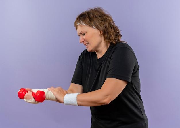 Donna sportiva di mezza età in maglietta nera con fascia tenendo il manubrio toccando il suo polso fasciato avendo dolore in piedi sulla parete blu