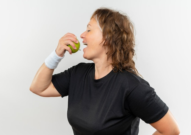 Middle aged sporty woman in black t-shirt with headband holding green apple biting it with happy face standing over white wall
