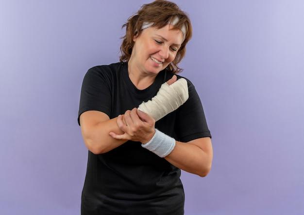 Donna sportiva di mezza età in maglietta nera con fascia che tiene il polso fasciato avendo dolore in piedi sopra la parete blu