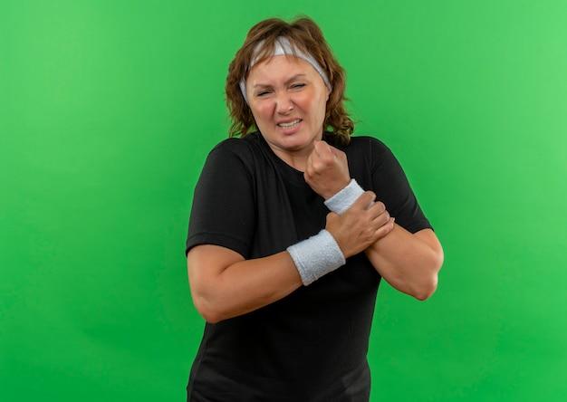Donna sportiva di mezza età in maglietta nera con fascia che tiene il polso fasciato che non sembra stare bene avendo dolore in piedi sopra la parete verde