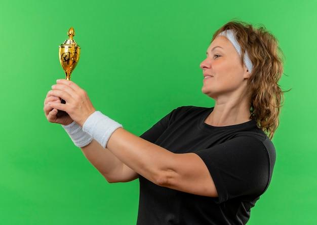 Donna sportiva di mezza età in maglietta nera con fascia tenendo il trofeo guardandolo con il sorriso sul viso in piedi sopra la parete verde