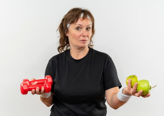 Middle aged sporty woman in black t-shirt with headband holding two green apples and dumbbells looking confused having doubts standing over white wall