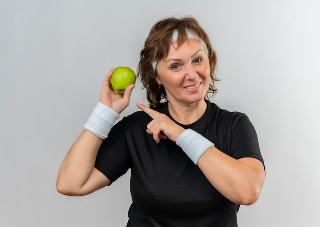 Middle aged sporty woman in black t-shirt with headband holding two green apples pointing with finger to them smiling cheerfully standing over white wall
