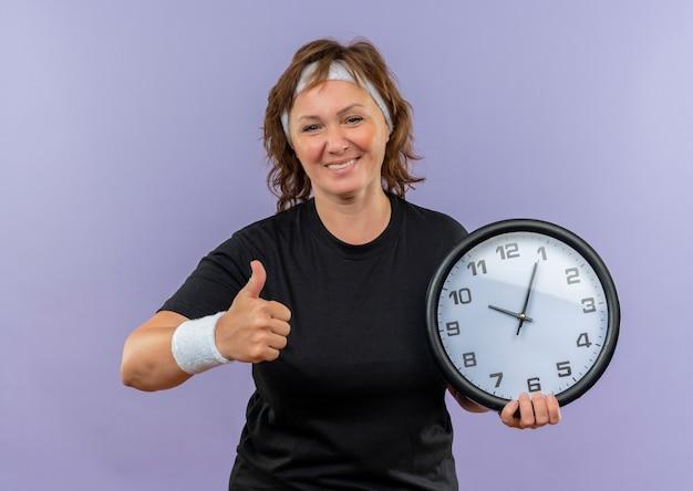 Donna sportiva di mezza età in maglietta nera con fascia tenendo l'orologio da parete sorridendo allegramente mostrando pollice in alto in piedi sulla parete blu