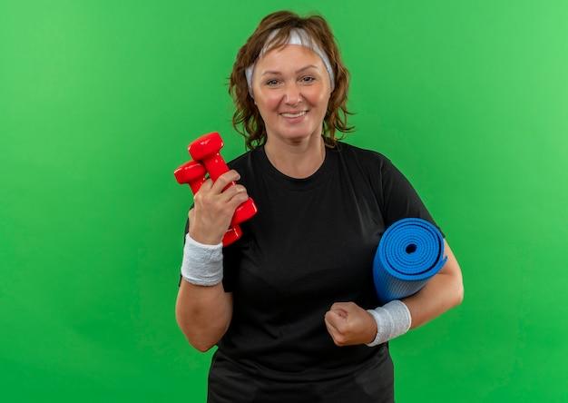 Donna sportiva di mezza età in maglietta nera con fascia che tiene materassino yoga e due manubri sorridenti con la faccia felice in piedi sopra la parete verde