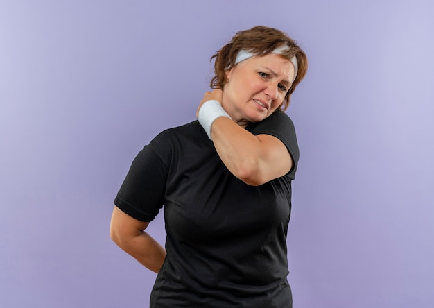 Middle aged sporty woman in black t-shirt with headband looking unwell touching her neck feeling pain standing over blue wall