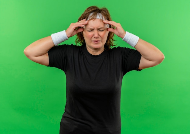 Middle aged sporty woman in black t-shirt with headband looking unwell touching temples suffering from headache standing over green wall