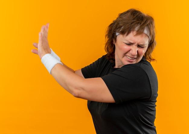 Donna sportiva di mezza età in maglietta nera con fascia che fa gesto di difesa con le mani in piedi sopra la parete arancione
