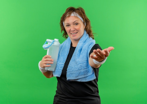 Middle aged sporty woman in black t-shirt with headband and towel on her neck holding bottle of water making come in gesture with hand smiling standing over green wall