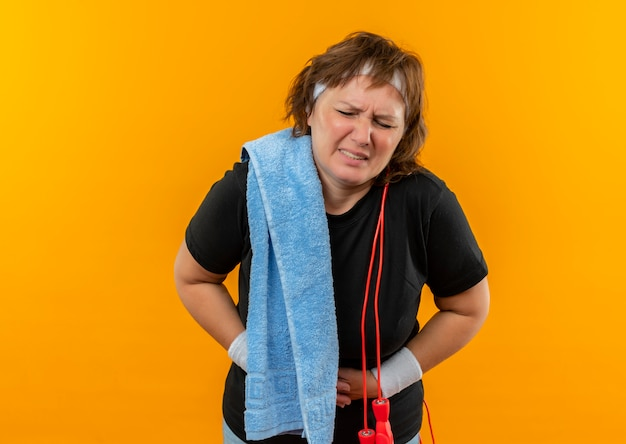 Middle aged sporty woman in black t-shirt with headband and towel on shoulder looking unwell touching her belly feeling pain standing over orange wall