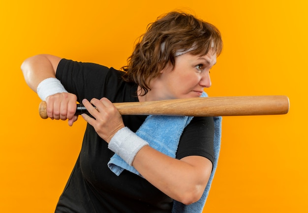 Middle aged sporty woman in black t-shirt with headband and with towel on shoulder holding basebal bat looking aside going to begin to play strained and confident standing over orange wall