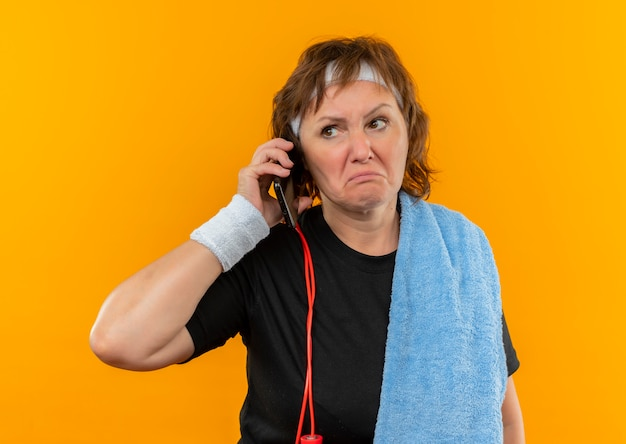 Middle aged sporty woman in black t-shirt with headband and with towel on shoulder listening to voice message looking confused standing over orange wall