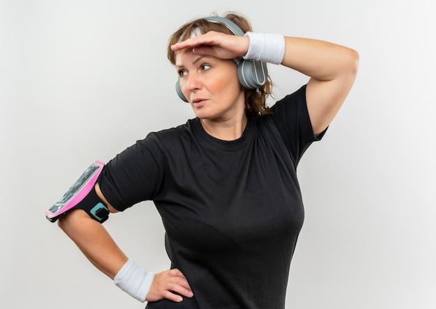 머리띠와 헤드폰이 흰색 벽 위에 서있는 심각한 얼굴로 머리 위로 손으로 옆으로보고있는 검은 색 티셔츠에 중간 나이 든 스포티 한 여자
