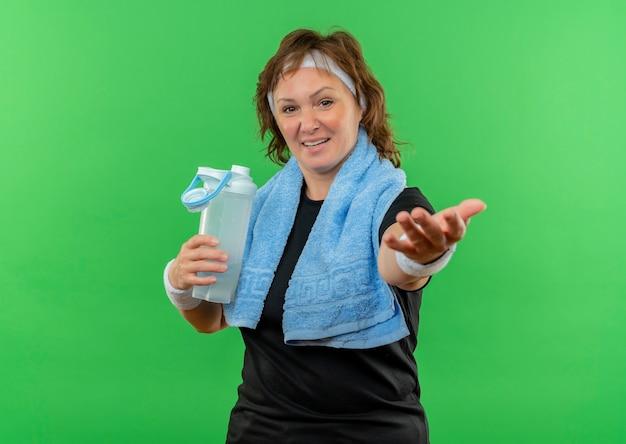 Спортивная женщина средних лет в черной футболке с повязкой на голову и полотенцем на шее держит бутылку воды, делая жест, улыбаясь рукой, стоя над зеленой стеной