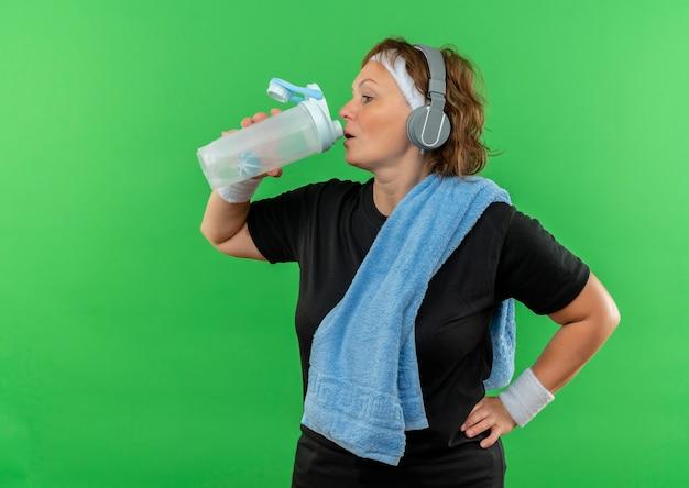 녹색 벽 위에 서있는 운동 식수 후 피곤해 보이는 그녀의 목에 머리띠와 수건이 달린 검은 색 티셔츠에 중간 나이 든 스포티 한 여자