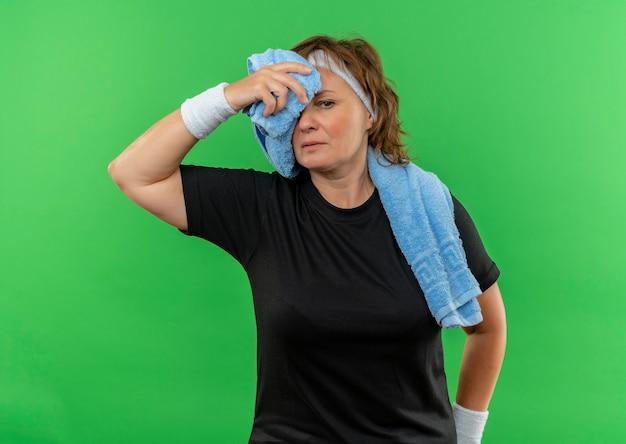 녹색 벽 위에 서있는 운동 후 피곤하고 지쳐 보이는 그녀의 목에 머리띠와 수건이 달린 검은 색 티셔츠에 중간 나이 든 스포티 한 여자