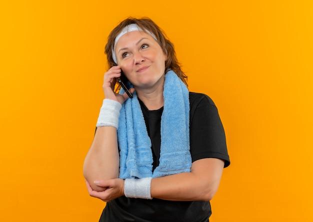 オレンジ色の壁の上に立って携帯電話で話している、幸せで前向きな脇を見て、肩にヘッドバンドとタオルが付いた黒いtシャツの中年のスポーティな女性