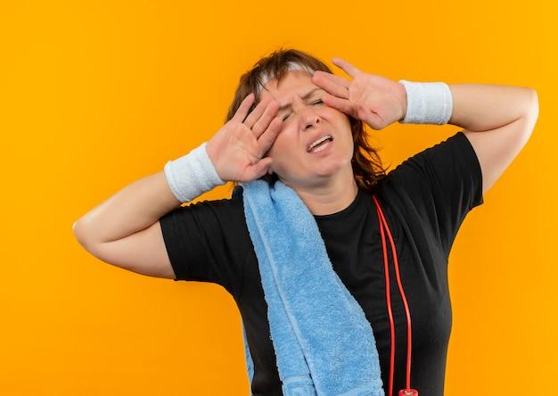 오렌지 벽 위에 서있는 작업 후 피곤하고 지쳐 보이는 어깨에 머리띠와 수건이 달린 검은 색 티셔츠에 중간 나이 든 스포티 한 여자
