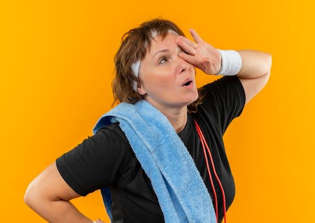 오렌지 벽 위에 서있는 운동 후 피곤하고 지쳐 보이는 어깨에 머리띠와 수건이 달린 검은 색 티셔츠에 중간 나이 든 스포티 한 여자