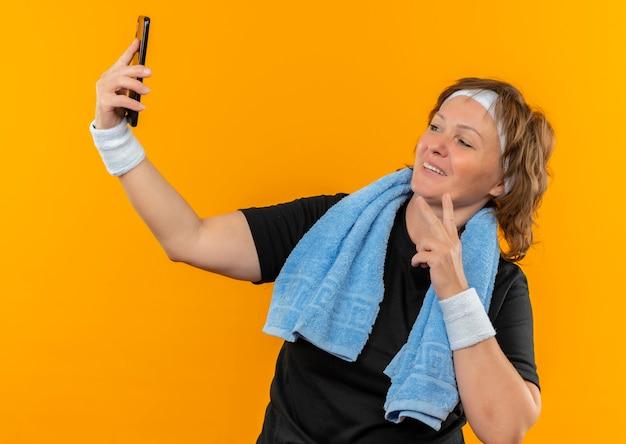 머리띠와 어깨에 수건이 달린 검은 색 티셔츠에 중간 나이 든 스포티 한 여자 오 오렌지 벽 위에 서있는 행복한 얼굴로 웃는 셀카를 복용하는 그녀의 스마트 폰