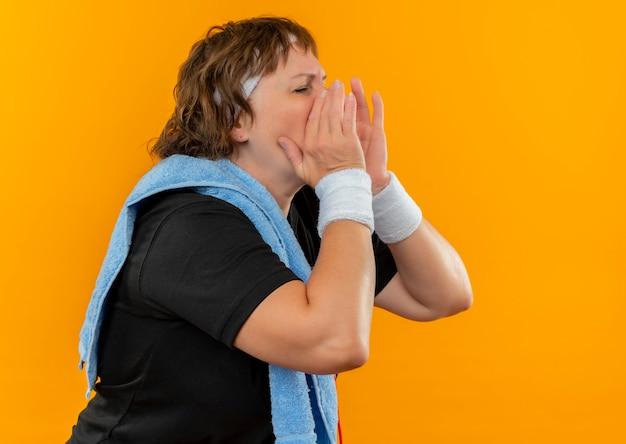 Спортивная женщина средних лет в черной футболке с повязкой на голову и с полотенцем на плече кричит или зовет руками возле рта, стоя над оранжевой стеной
