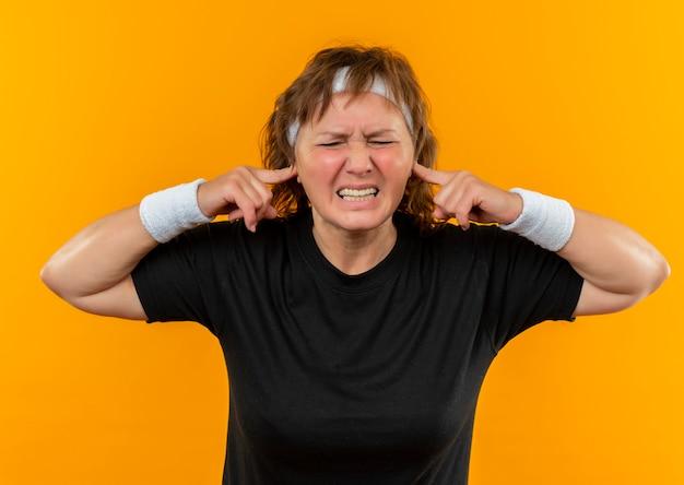 오렌지 벽 위에 서있는 성가신 표정으로 손가락으로 귀를 닫는 머리띠와 검은 색 티셔츠에 중간 나이 든 스포티 한 여자