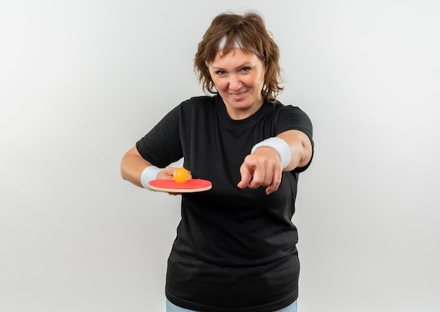 Спортивная женщина средних лет в черной футболке с повязкой на голове держит ракетку с мячом для настольного тенниса, указывая пальцем в камеру, улыбается со счастливым лицом, стоящим над белой стеной