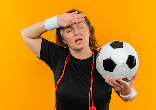 Спортивная женщина средних лет в черной футболке с повязкой на голове, держащая футбольный мяч, выглядит уставшей и перегруженной, стоя у оранжевой стены