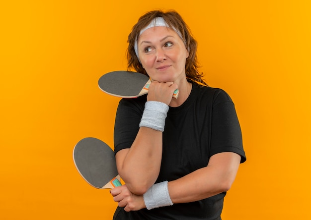 Спортивная женщина средних лет в черной футболке с повязкой на голове держит две ракетки для настольного тенниса, смотрит в сторону, улыбается и думает, стоя у оранжевой стены