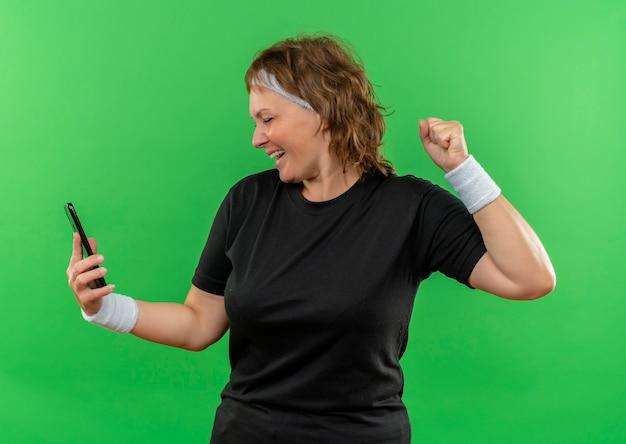 Спортивная женщина средних лет в черной футболке с повязкой на голове смотрит на экран своего мобильного сжимающего кулака, счастливая и взволнованная, стоя у зеленой стены