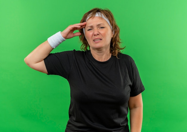 緑の壁の上に立って体調不良で疲れているように見えるヘッドバンド付きの黒いtシャツの中年のスポーティな女性