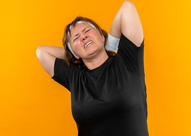 오렌지 벽 위에 서있는 통증이있는 그녀의 목을 만지고있는 머리띠가있는 검은 색 티셔츠에 중간 나이 든 스포티 한 여자