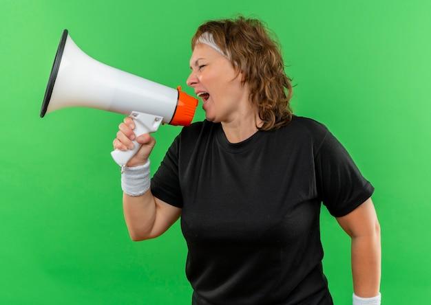 Спортивная женщина средних лет в черной футболке с повязкой на голове кричит в мегафон с агрессивным выражением лица, стоя у зеленой стены