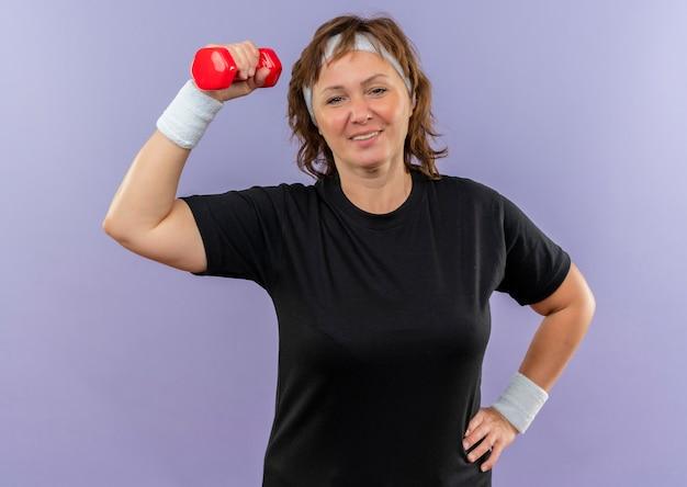 파란색 벽 위에 자신감 서 찾고 아령으로 운동 머리띠와 검은 티셔츠에 중간 나이 든 스포티 한 여자