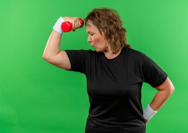 녹색 벽 위에 자신감 서 찾고 아령으로 운동 머리띠와 검은 티셔츠에 중간 세 스포티 한 여자