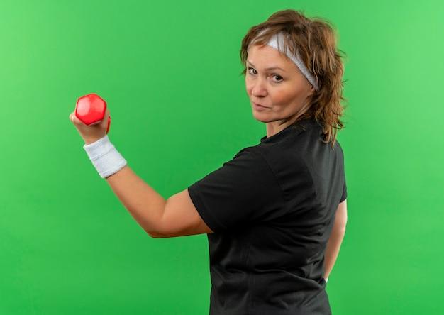 Спортивная женщина средних лет в черной футболке с повязкой на голове, тренируется с гантелями, уверенно выглядит, стоя у зеленой стены
