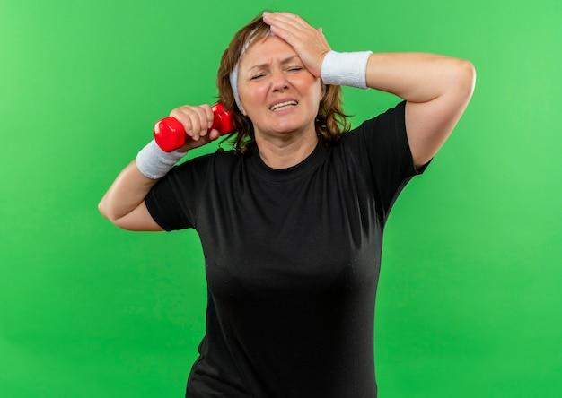 Спортивная женщина средних лет в черной футболке с повязкой на голове тренируется с гантелями, выглядит усталой и измученной, стоя у зеленой стены
