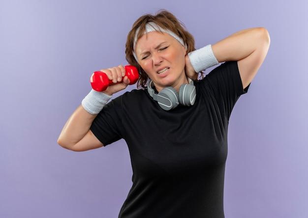 Спортивная женщина средних лет в черной футболке с повязкой на голове, тренирующаяся с гантелями, выглядит усталой и измученной, касаясь ее шеи, чувствуя боль, стоя у синей стены