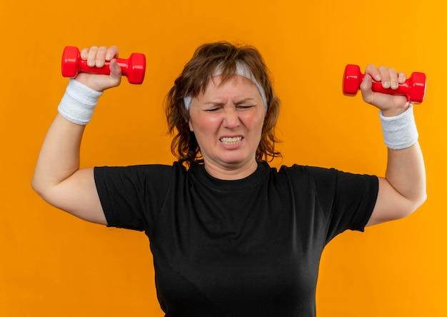오렌지 벽 위에 자신감과 긴장 서 찾고 아령으로 운동 머리띠와 검은 색 티셔츠에 중간 나이 든 스포티 한 여자