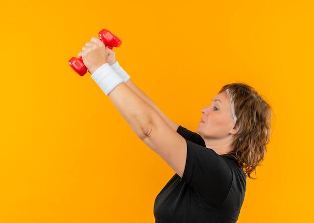 오렌지 벽 위에 자신감과 긴장 서 찾고 손을 올리는 아령으로 운동하는 머리띠와 검은 색 티셔츠에 중간 세 스포티 한 여자