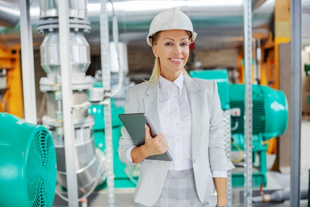 Middle-aged successful blond female supervisor in suit with protective helmet on head standing in power plant with tablet