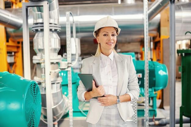 中年の成功した女性ceoは、ヘルメットを頭にかぶって、タブレットを手に暖房設備に立って、笑顔でカメラを見ています。