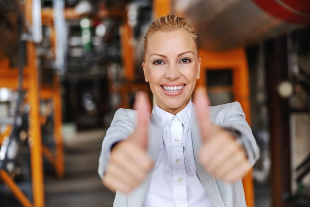 Middle aged successful independent female ceo in suit standing in heating plant and showing thumbs up