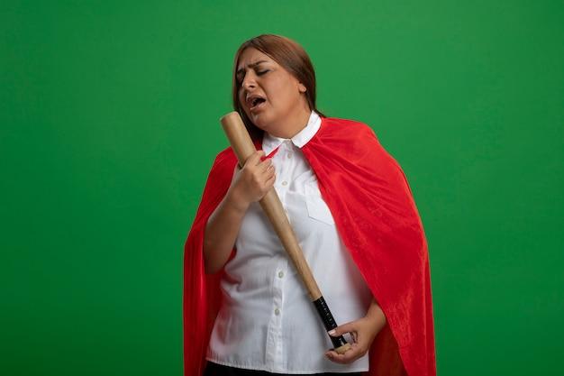 野球のバットを持って目を閉じて、緑に孤立して歌う中年のスーパーヒーローの女性