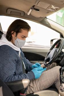 Водитель такси средних лет в тканевой маске и перчатках работает с мобильным приложением во время езды