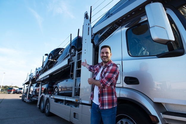 Дальнобойщик средних лет перед прицепом грузовика с автомобилями