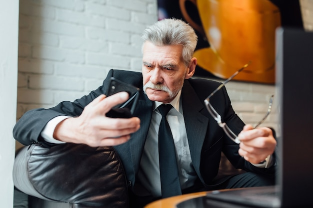 Middle-aged unhappy businessman in modern restaurant using laptop and phone.