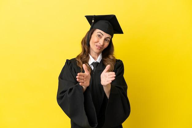 Выпускник университета среднего возраста изолирован на желтом фоне аплодирует после выступления на конференции