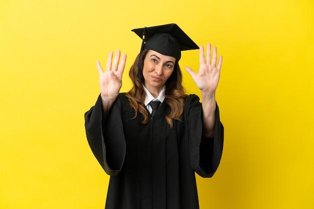 Выпускник университета среднего возраста изолирован на желтом фоне, считая девять пальцами